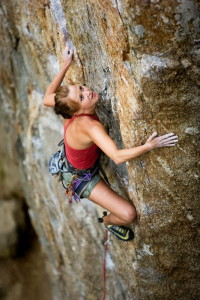 An eager female climber on a steep rock face looks for the next hold - viewed from above. Shallow depth of field is used to isolated the climber.